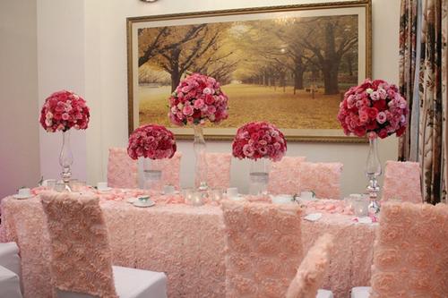 Trong nhà, bàn tiệc được trang trí với những bình hoa cao là nơi gia đình nhà gái tiếp đãi gia đình chú rể Nguyễn Đức Hải.