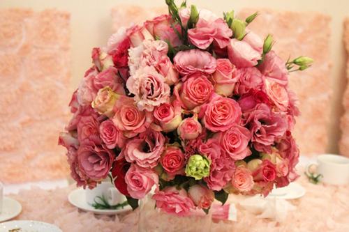Hoa trên bàn tiệc được kết từ hoa hồng và lan tường nhẹ nhàng.