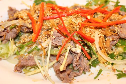 Đây là món ăn sống với thịt bò tái chanh, kết hợp vị chua chua từ khế, vị hơi chát của chuối xanh, và mùi thơm từ hành sim hòa lẫn vừng rang vàng.
