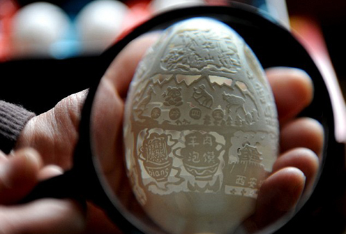 Wen Fuliang has practiced eggshell carving for more than ten years. Egg carving is done using a fine diamond bit on an electric rotary tool. The artist sketches a design on the shell, which has been carefully emptied of the yolk and egg white with a syringe.