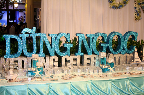 Tên cô dâu chú rể với màu xanh biển nổi bật là chi tiết gây ấn tượng nhất trên bàn đón tiếp.