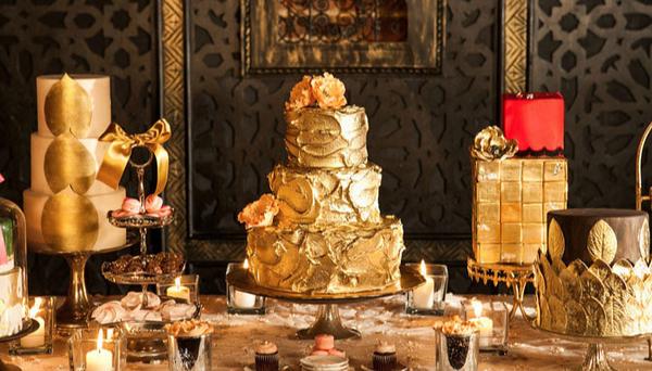 Bàn đặt bánh cưới với những chiếc bánh trang trí với sắc màu kim loại vàng ánh.