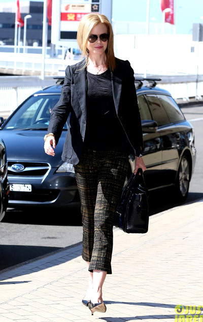 Nicole Kidman flashes a smile as she heads inside the airport to catch a departing flight on Thursday (January 3) in Sydney, Australia.