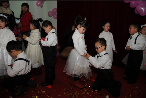 Little grooms knelt down to wear rings for their little brides.