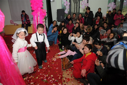 According to Li, head of the kindergarten, many kids of age 3 to 6 started to grow sensitive about marriage. For example, boys would say I like you to girls. Girls would buy candies for boys that they like. Some kids would even mention getting married. The group wedding activity was to teach the kids a healthy view of marriage.