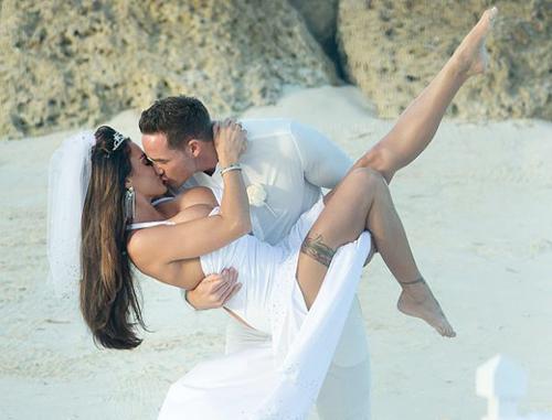 Chú rể nhấc bổng cô dâu và trao nàng nụ hôn nồng nàn, đắm đuối giữa khung cảnh lãng mạn trên bờ biển.