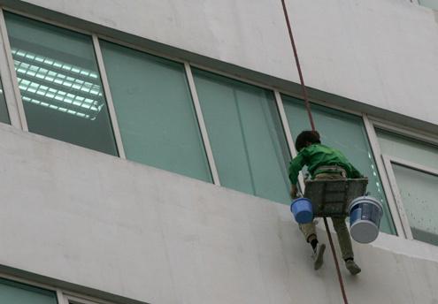Bộ đồ để hành nghề với những công nhân làm nghề 'nguy hiểm' này là một tấm ván ép nhỏ, được buộc vào một sợi dây thừng, một thùng sơn và xô nước nhỏ.
