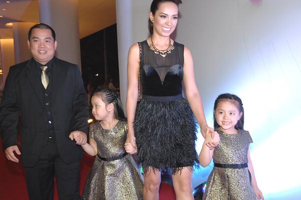 Hai bé Suli- Suti được bố mẹ cho mặc hai bộ đầm giống nhau màu ánh kim, ton sur ton với váy đen của mẹ.