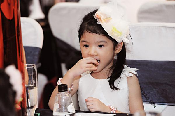 Trong lúc đêm trao giải đang diễn ra, cô bé ngồi ăn.
