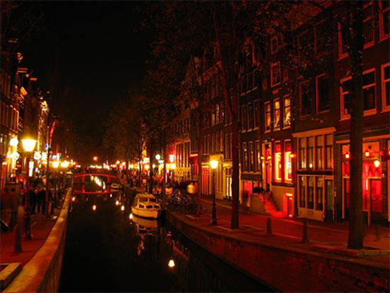 """Khu đèn đỏ De Wallen ở thành phố Amsterdam, Hà Lan được cho là khu đèn đỏ nổi tiếng nhất thế giới. Nơi đây có vài trăm căn phòng nhỏ, trong đó các cô gái ăn mặc """"mát mẻ"""" với các tư thế khêu gợi đứng sau lớp kính, mời chào khách."""