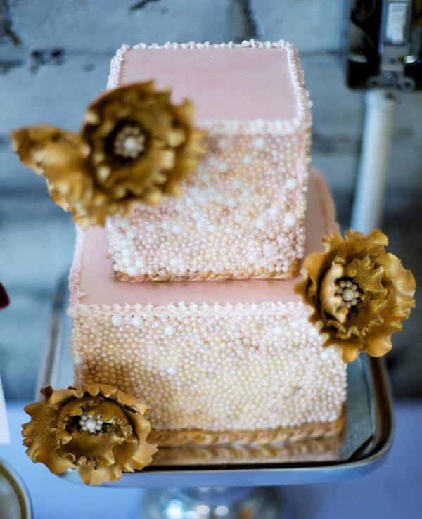 Ba bông hoa màu vàng kim tạo vẻ sang trọng cho chiếc bánh cưới hồng.