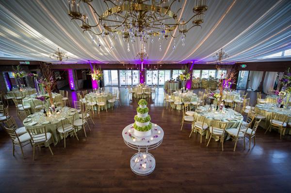 Không gian đám cưới có sắc tím của đèn, và màu xanh của ánh cùng hoa bàn tiệc.