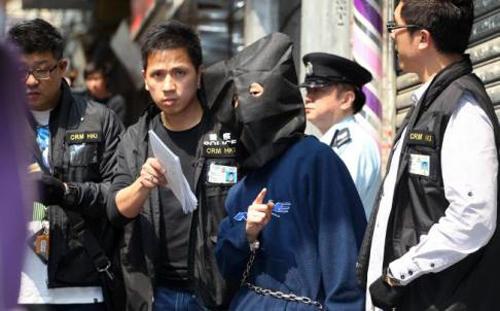 Gã con trai bị cảnh sát bắt đeo mặt nạ trước khi bị giải đi. Ảnh: SCMP