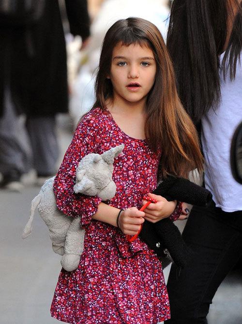 Suri ôm thú bông đi chơi trên phố New York hôm 29/3. Cô bé có diện mạo mới mẻ bởi tóc mai đã được cắt ngắn ngủn.