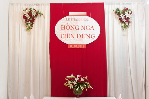Tất cả mọi chi tiết đều giản tiện, để làm nổi bật phong cách trang nhã. Ngoài bình hoa lo kèn lớn đặt ở trung tâm bàn, trên phông trắng còn treo hai cụm hoa loa kèn và hồng đỏ.