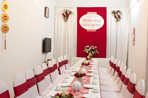 Các trang trí tại nhà của cô dâu Hồng Nga mang phong cách cổ điển, với phông trắng, kết hợp cùng vải đỏ và bảng chữ in đơn giản.