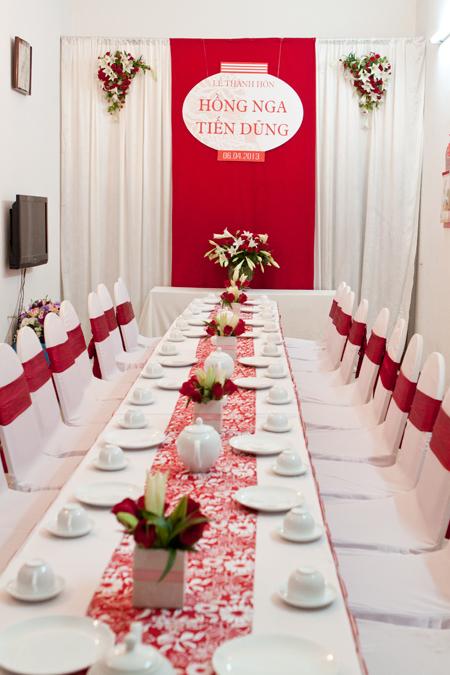 Bàn tiệc được phủ khăn trải bàn trắng và table runner hoa đỏ trang nhã.