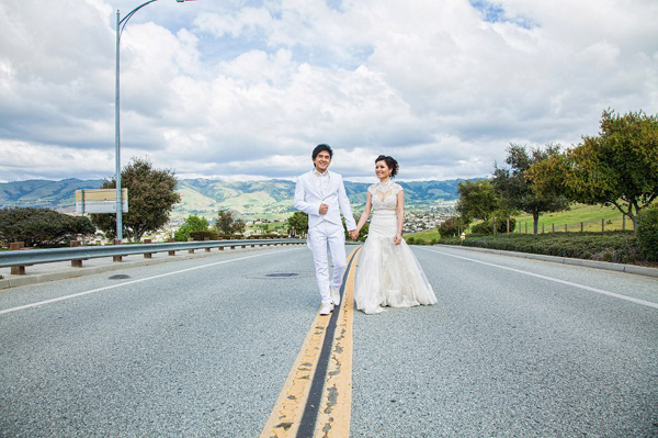 Trong bức ảnh cưới thứ 2, cặp đôi nắm tay nhau và cười rạng ngời trên đường quốc lộ.