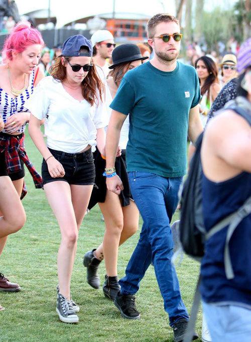 Kristen bám nhẹ vào tay bạn trai khi cả hai vội vã chạy tới sân khấu xem các nhóm nhạc trình diễn.
