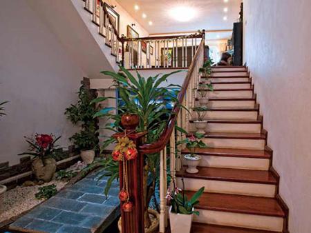 """Cầu thang với những bình hoa xinh xắn dẫn lối lên phòng khách. Ngoài ra còn có một cầu thang ở bên ngoài sân để """"cơ động"""" và linh hoạt hơn trong việc sử dụng."""