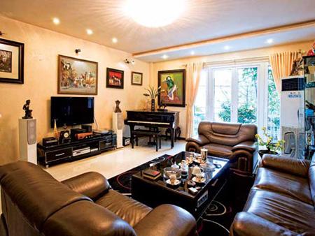 Phòng khách dành phần lớn diện tích cho bộ sofa bằng da bóng nhoáng. Chiếc bàn màu đen hai ngăn khổ lớn, rất hợp lý với những ngôi nhà có phòng khách rộng. Từ phòng khách có thể phóng tầm mắt ra bên ngoài ô cửa màu trắng vô cùng sang trọng và bình yên.