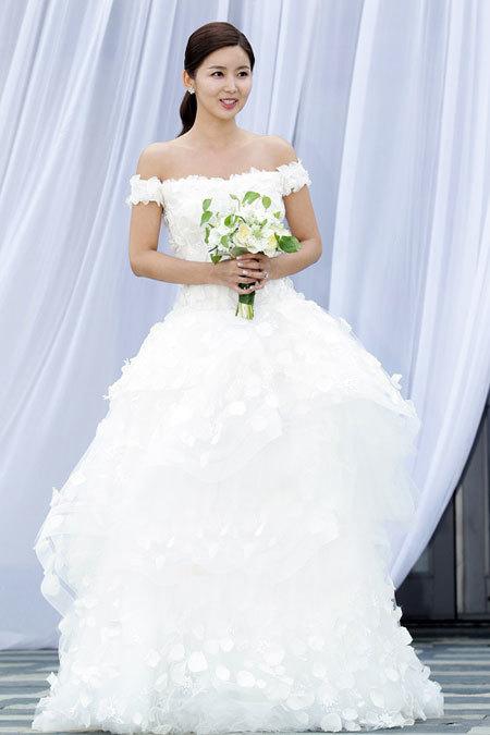 Vì váy cưới quá cầu kỳ nên cô dâu chọn trang điểm nhẹ nhàng và buộc tóc đơn giản.