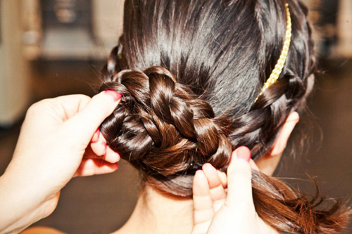 Tiếp tục quấn tròn đuôi tóc vừa tết để tạo thành búi tóc thấp sau gáy. Bạn vẫn dùng cặp ghim để cố định.