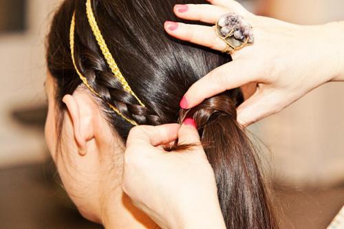 Lấy lọn tóc vừa tết ở bên phải, quấn quanh chun buộc tóc. Sau đó, lồng một dải dây ruy băng