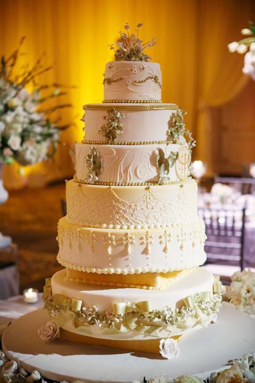 Bánh cưới được trang trí với những họa tiết và phụ kiện cầu kỳ, mang sắc trắng - vàng nhạt.