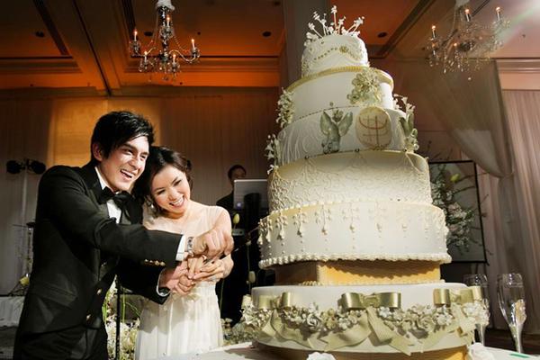 Cô dâu chú rể tươi tắn cùng nhau cắt bánh cưới.