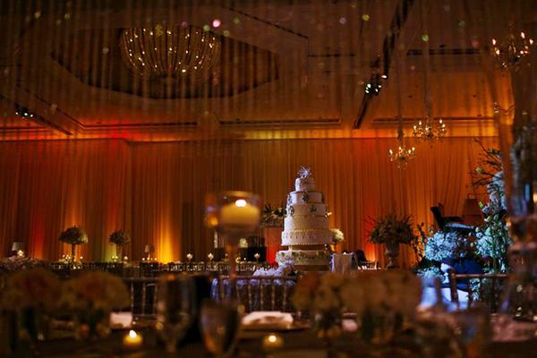 Bánh cưới được đặt ở gần sân khấu, cao và nổi bật.