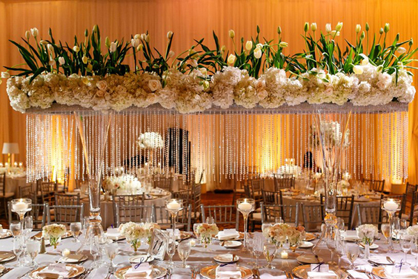 Còn bàn tiệc dài lại ấn tượng với thiết kế hoa treo. Những chùm hoa cẩm tú cầu, kết hợp cùng hoa hồng, hoa tulip và dải pha lê lung linh làm không gian thêm phần sang trọng.