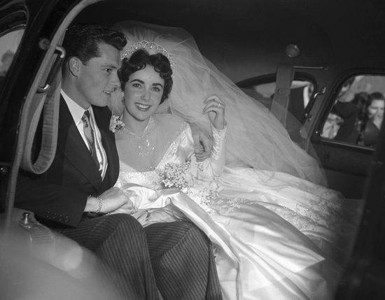 Elizabeth Taylor kết hôn 8 lần nhưng đám cưới đầu tiên với Conrad Hilton vào năm 1950 luôn được nhớ đến nhiều nhất nhờ chiếc váy cưới may bằng satin cầu kỳ mà cô chọn. Chiếc váy có giá 1.500 USD, một con số khổng lồ ở thời điểm đó.