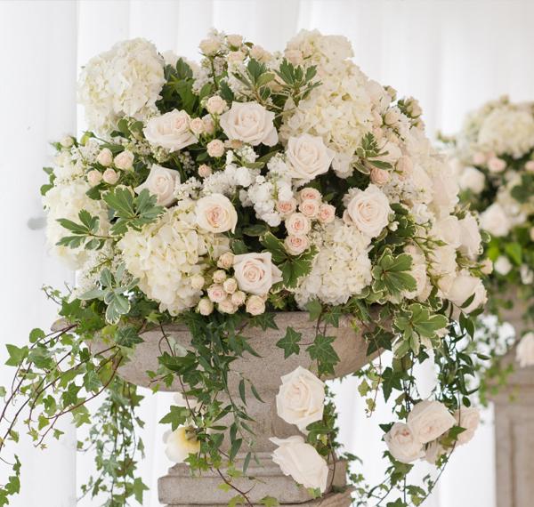 Những bình hoa cao tỏa tròn được kết từ cẩm tú cầu, hoa hồng, hồng tỉ muội và các loại lá rủ mềm mại.