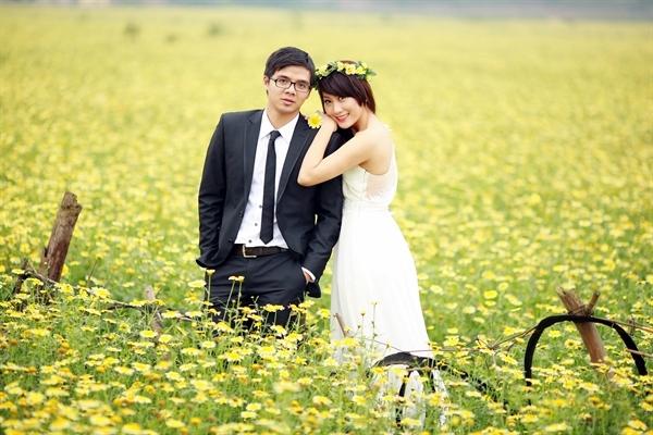 """Những cánh đồng hoa là địa điểm chụp ảnh ngoại cảnh được nhiều cô dâu chú rể ưa chuộng. Trong bộ ảnh """"Kỷ niệm của chúng mình"""", đôi uyên ương chọn cánh đồng hoa cải cúc để ghi lại những bức hình lãng mạn."""