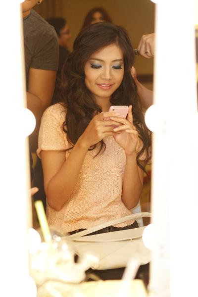 Người đẹp Biển của cuộc thi Hoa hậu Việt Nam 2012 Ninh Hoàng Ngân chăm chú vào chiếc điện thoại khi đang chờ làm tóc, trang điểm.