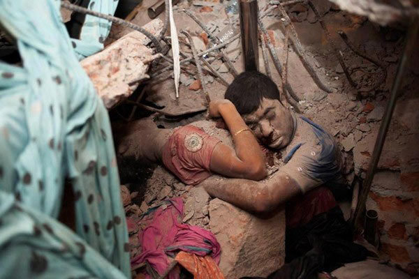 Bức ảnh của nhiếp ảnh gia Taslima Akhter ghi lại cảnh tượng đôi nam nữ ôm nhau chết, trên mặt nam thanh niên còn hiện lên dòng máu nóng thật sự khiến người xem không khỏi chua xót và nhói lòng.