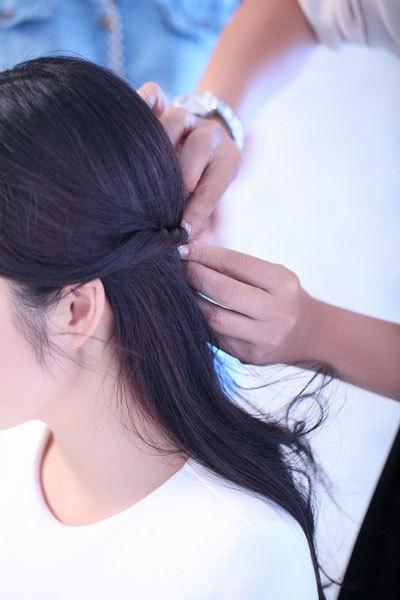 Dùng lược phân chia hai lọn tóc ở bên tai, xoắn theo chiều kim đồng hồ ra phía sau gáy rồi dùng ghim cố định lại.