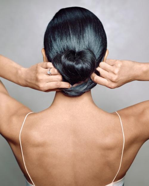 Quấn phần đuôi tóc giữ lại ở trên xung quanh chun buộc. Đồng thời, kéo nhẹ phần vòng tròn sang hai bên để tạo thành búi tóc phồng và dùng cặp ghim cố định lại.