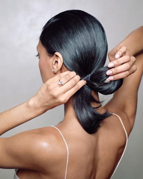 Dùng chun buộc đuôi tóc thấp sau gáy. Ở vòng buộc cuối cùng, giữ lại một phần đuôi tóc để tạo thành vòng tròn.