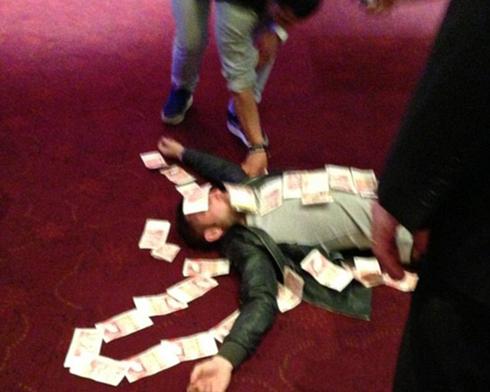 Phil Bardsley nằm 'bất tỉnh' bên những tờ tiền. Ảnh: Mirror.