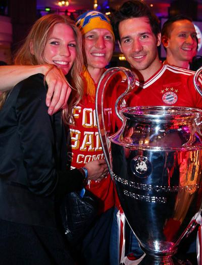 Schweinsteiger một tay ôm bạn gái, tay ôm các đồng đội chụp ảnh bên cạnh Cup.