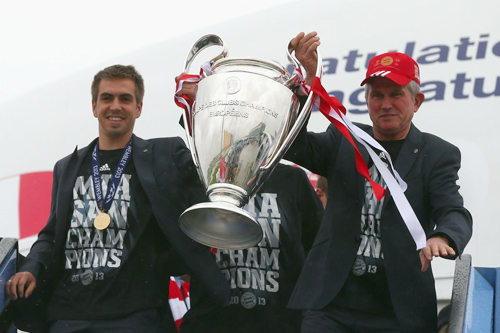 Philipp Lahm và HLV Juup Heynckes cầm Cup đi đầu khi ra khỏi máy bay.