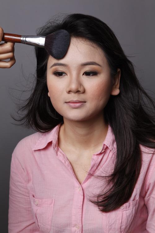 Phủ phấn highlight lên các điểm nổi bật trên khuôn mặt như trán, cằm, gò má, sống mũi.