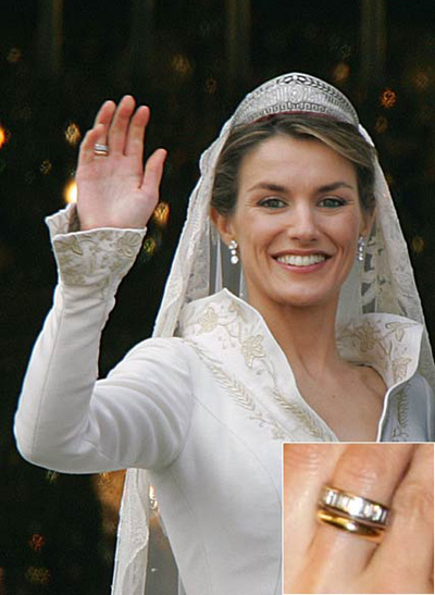 Princess Letizia of Spain wears a 16 baguette diamond engagement ring with a white gold trim, nestled next to her gold wedding ring.