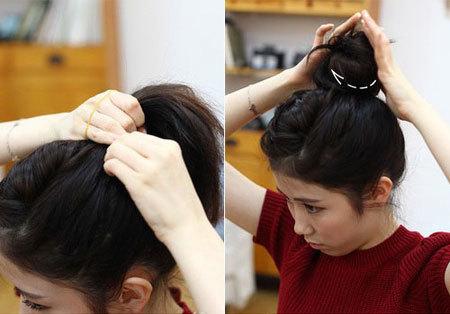 Bước 6: Dùng chun vòng buộc cao lọn tóc phía sau, rồi quấn đuôi tóc, tạo thành một búi trên đỉnh đầu.