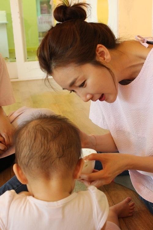 Choi Ji Woo cho một em nhỏ ăn. Chưa từng làm mẹ nhưng nữ diễn viên nổi tiếng ân cần, chu đáo với các em bé,