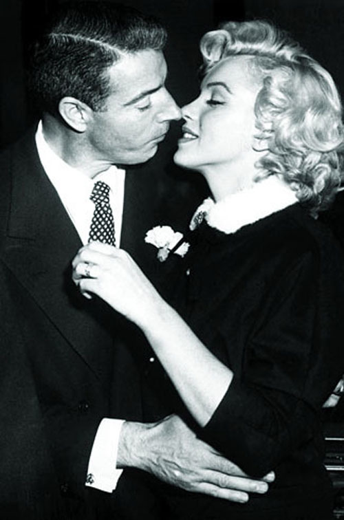 Marilyn Monroe trong bộ váy ngắn có áo khoác màu đen.