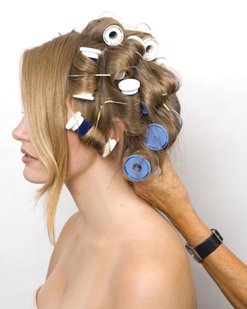 Chia tóc thành nhiều lọn nhỏ và dùng lô điện để uốn xoăn. Lưu ý để riêng phần tóc mái.