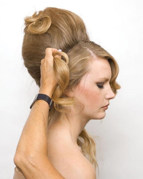 Cuộn phần tóc vừa đánh rối theo hướng từ phải sang trái để tạo thành búi tóc trên đỉnh đầu. Sau đó, dùng cặp ghim và gôm xịt giữ dáng tóc.
